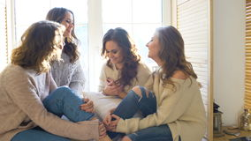 Four beautiful girls discuss smile sitting on window. Girlfriends having fun and laugh in bedroom stock video footage