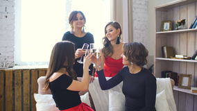 Four beautiful girls drink champagne and cheers. Women having fun laugh in bedroom. stock footage