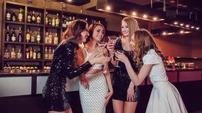 Four beautiful girls drinking at a nightclub stock footage