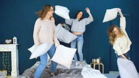 Four beautiful girls fight pillows each other . Girlfriends having fun and laugh in bedroom stock footage