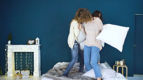 Four beautiful girls fight pillows each other . Girlfriends having fun and laugh in bedroom stock video footage