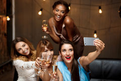 Four beautiful girls making selfie at party. Royalty Free Stock Photography