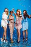Four beautiful girls resting at party over blue background. Royalty Free Stock Images
