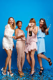 Four beautiful girls resting at party over blue background. Four young beautiful girls in dresses drinking champagne, smiling, laughing, resting at party over Royalty Free Stock Image