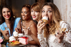 Four beautiful girls resting at party. Four young beautiful girls in dresses eating cakes, smiling, laughing, drinking champagne, resting at party Stock Images