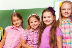 Four beautiful girls stand close in classroom Stock Photography