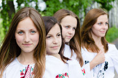 Four beautiful girls standing in line on green outdoors background Stock Images