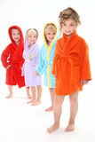 Four beautiful kids in bathrobes. Cute kids dressed in bathrobe on the white background Stock Images