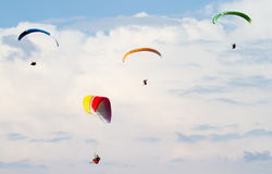 Four beautiful paragliders in the cloudy sky Stock Photography