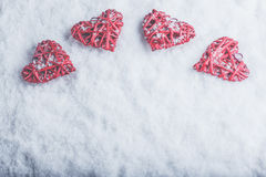 Four beautiful romantic vintage hearts on a white frosty snow background. Love and St. Valentines Day concept. Royalty Free Stock Image