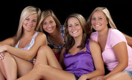 Four beautiful sisters. Four beauituful young sisters sitting together on a couch royalty free stock photography