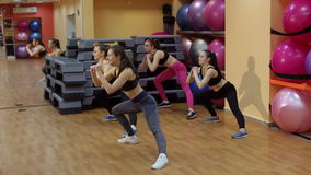 Four beautiful sports girls squats in the gym. stock video