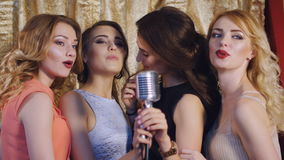 Four beautiful stylish girls singing karaoke at the club stock footage