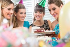 Four beautiful women and best friends smiling while sharing a birthday cake. Four beautiful women and best friends smiling while sharing a tasty birthday cake royalty free stock photos