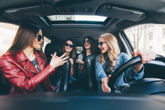 Four beautiful young cheerful women looking happy and playful while sitting in car stock photos