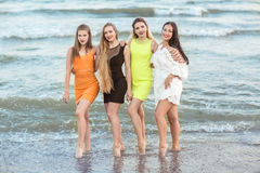 Four beautiful young girls stand in the background of a sea shore, full-lengths. Charming young women in multi-colored Royalty Free Stock Photos