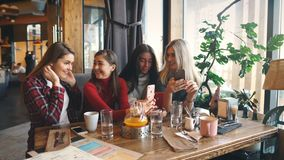 Four beautiful young woman doing selfie in a cafe, best friends girls together having fun. Posing emotional lifestyle people concept stock video