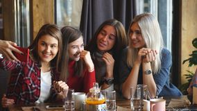 Four beautiful young woman doing selfie in a cafe, best friends girls together having fun. Posing emotional lifestyle people concept stock video footage