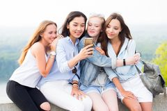Four beautiful young women using smartphone and smiling in the Park, outdoor royalty free stock photography