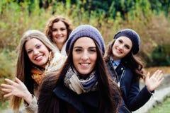Four beautiful young women waving Royalty Free Stock Photos