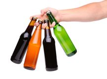 Four beer bottles in different colours and hand stock image
