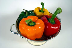 Four  Bell Peppers. Red, Orange, Yellow, and green bell peppers in a collander Stock Photos