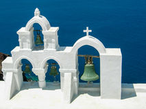 Four bells in Santorini. Four bells by a church in Santorini, Greece with the blue sea in the bwackground stock photo
