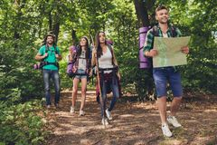Four best friends are walking in autumn  forest. Amazed by the beauty of nature, wearing comfortable outfits for hiking, sneakers, hats, have backpacks Royalty Free Stock Photos