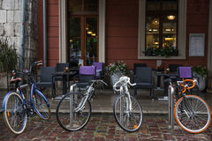Four bicycles parked on the front of the cafe in the rain stock photos
