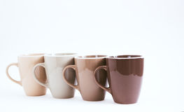 Four big cups on a white background. Not isolated, color gradation, selective focus Stock Image
