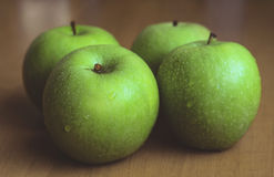 Four big green apples Stock Photography