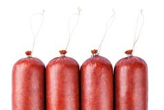 4 sticks of sausage with fastenings. Four big sticks of sausage with fastenings are isolated on a white background for execution of price tags, the menu and stock photos
