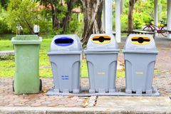 Four bins are on the sidewalk in the park. Stock Photo