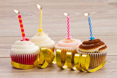 Four birthday cupcakes on table. Four birthday cupcakes with burning candles on wooden table Royalty Free Stock Photography