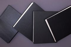 Four black books on a gray Royalty Free Stock Photography