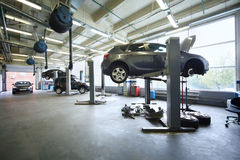 Four black cars in garage with special equipment royalty free stock photo