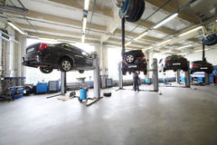 Four black cars on lifts in small service station Stock Photos