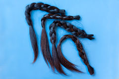 Four black chopped-off braids of human hair Royalty Free Stock Images