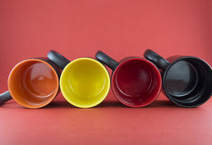 Four black cup with a colored bottom Stock Image