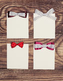 Four blank paper sheets. With colorful bows on wooden background Royalty Free Stock Photography