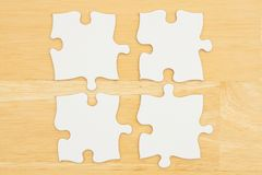 Four blank puzzle pieces on textured desk wood background royalty free stock images