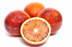 Four blood oranges, one is sliced Stock Photos