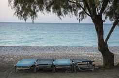 Four blue beach chairs on a beach under a tree Stock Photography