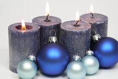 Four blue candles and blue christmas tree balls Stock Photos