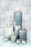 Four blue, grey and white burning christmas candles with snow in Stock Images