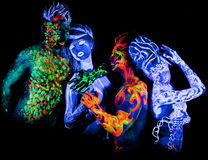 Four - Body art glowing in ultraviolet light Royalty Free Stock Images
