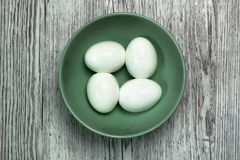 Four boiled eggs in a bowl on a grey wood top view royalty free stock image
