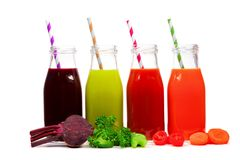 Four bottles of beet, greens, tomato, and carrot juice with ingredients, isolated. Four bottles of vegetable juice, beet, greens, tomato, and carrot with Royalty Free Stock Image