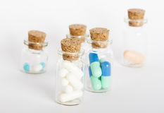 Four bottles with colorful pills. Five glass bottles with colorful pills and coks Stock Photography