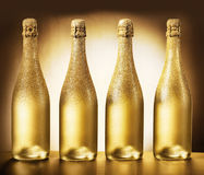 Four bottles of golden champagne. Four elegant unlabeled bottles of luxury golden champagne over a highlighted brown background with frosted necks and glowing Stock Photos